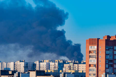 Smoke in the sky above the houses. Fire in the city. Smoke from the fire rises into the sky. Extraordinary incident. Trouble. Misfortune. Gray-black smoke against the blue sky.
