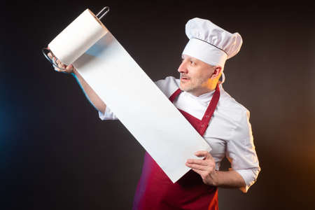 The satisfied chef unwinds the towels from the roll. Guest service in the restaurant. Hospitality. Maintaining sanitary standards. A man in a chef's uniform with napkins in his hands.
