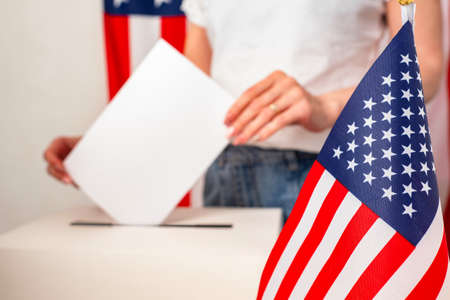 Voting in elections in the United States. The American woman puts the ballot in the basket. A woman expresses her opinion in elections. American flag and a girl with a ballot in her hands.