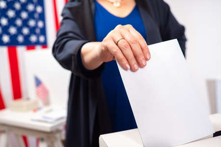 Elections in the United States. Hand with a ballot close-up. Voting woman on the background of the American flag. Politics.