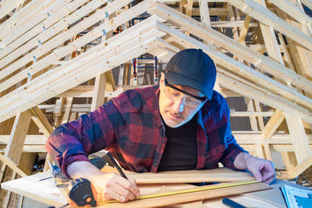 Carpentry work in construction. Carpenter on the background of the roof of a cottage under construction. The man is engaged in woodworking. Markings of the wood. 版權商用圖片