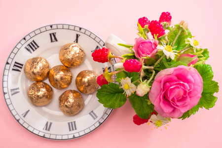 Time to enjoy life. Joy of life. Postcard with flowers and sweets. Bouquet of flowers and berries. Candy on a plate with a dial. A small present.