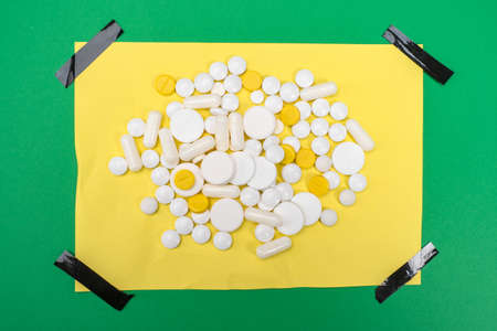 The tablets are on a yellow sheet of paper with black adhesive tape. Prescribing medications by a doctor. Treatment regimen. Follow the doctor's instructions.