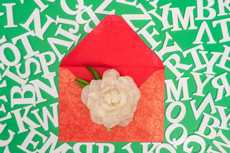 Writing letters. Envelope, letters and a flower on a green background. Congratulations in the letter. Colorful greetings. Greeting poems.