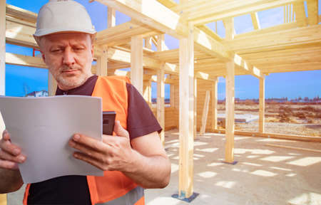 Construction of a country house. A Builder in a white helmet studies construction plans. Engineer on the background of the building frame. A man in an orange vest on a construction site.
