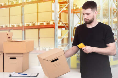 Warehouse inventory. The man checks the availability of the product in the warehouse. Recalculate the product using a barcode reader. Check the availability of goods.