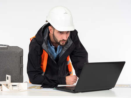 Construction concept on a white background. A civil engineer looks at the details of the project on his laptop. A man in a construction helmet at a table with a layout of the house and drawings.