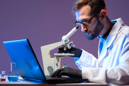 A microbiologist with a microscope and a laptop. A man makes notes on his laptop about the progress of chemical research. Microbiological developments. Biologist at the Desk.