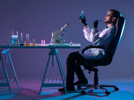Chemist in profile at the Desk. The chemist at the table is removed from the side. The scientist evaluates the result of a chemical experiment. A man sits at his Desk and examines a chemical liquid.