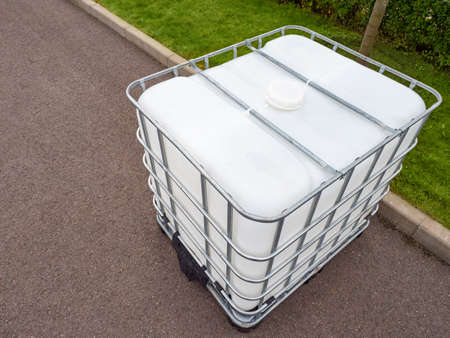 White plastic water tank. Barrel with a metal frame. Water supply on the street. Containers for transporting and storing liquids.