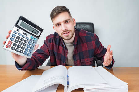 The man looks at the camera and shows the calculator. Fair price. Error in calculations. Cheating the customers. The auditor found errors. Negligence. Scam. Stockfoto