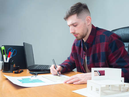 A man in a checked shirt studies the layout of the house. Construction documentation for the cottage. Design project of a new house. Work of an engineer in construction. Architect at the table.