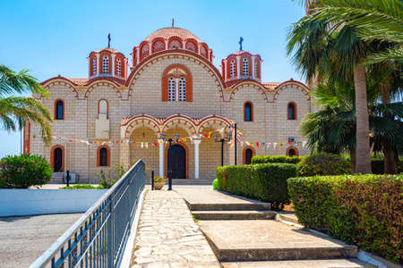 Cyprus. Protaras. Paralimni. St. Barbara's Church is decorated with flags. Orthodox Church with a terracotta roof. Attraction Of Protaras. Sunny day in Cyprus. Christianity. Mediterranean architecture Stok Fotoğraf