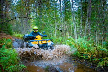 A man rushes on an ATV on a forest road. Yellow ATV drives through a puddle on a forest road. Cross-country racing. Quad bike racing. Extreme ATV riding. Rider on a Quad bike in the forest.