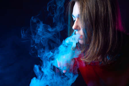 Portrait of a vaper girl in profile. A girl with an electronic cigarette in a cloud of smoke. A woman with an e-cigarette on a dark background with space for text. A long-haired girl smokes a VAPE.