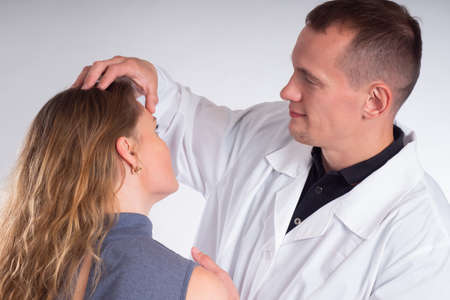 A man in a white coat examines the girl forehead. The doctor sees the patient. The man works as a cosmetologist. Examination of the patient.