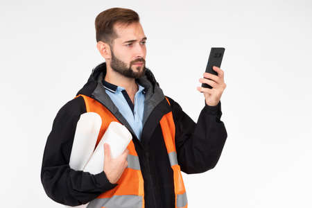 Engineer with drawings and smartphone on a white background. A man looks at the details of a construction project on his phone. The architect controls the progress of construction.