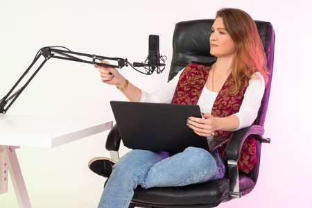 A girl with a laptop and a microphone. A woman records a podcast. The girl is sitting in a free position in a chair in front of the microphone. Host of a radio program.