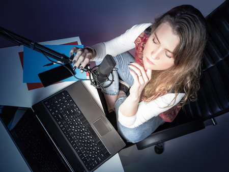 The girl in front of the Studio microphone is photographed from above. The girl is sitting in a free position in front of the microphone and is broadcasting. Recording Studio at home.