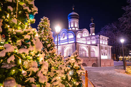 Christmas in Russia. Church and Christmas tree with decorations. Snow-Covered Moscow. New Year Moscow. Festive evening in the capital of the Russian Federation.Christmas tree with toys near the Church 版權商用圖片