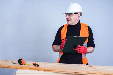 The carpenter clarifies the details of the project and makes notes. A man in a construction helmet next to lumber. Carpentry work in construction. Standard-Bild