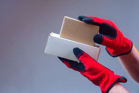 Hands in work gloves with two cardboard boxes. Shipping materials. Packaging. Storage. Cardboard packaging. Storage box.