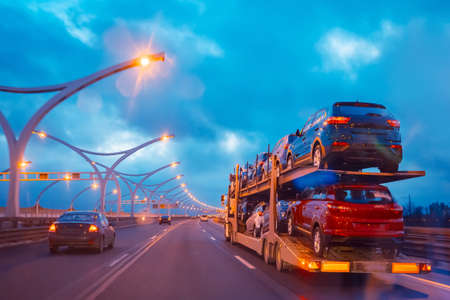 Transportation of passenger cars. Sale of passenger cars. Auto-trawl on the road. Sale of transport. Evening traffic on the motorway.