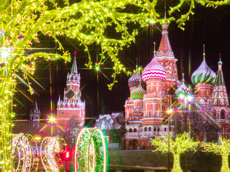 Happy New year greeting card. Garlands on the streets of Moscow. Christmas greetings from Russia. Luminous decor and the Moscow Kremlin. The Kremlin and St. Basil Cathedral on new year eve.