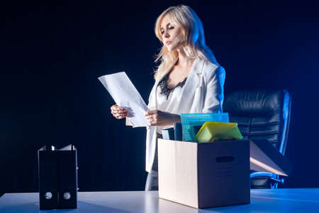A woman reads a dismissal order. The loss of a job. Sad girl with a box of office supplies. Loss of livelihood. The concept of mass reductions. Reduction of the company staff.