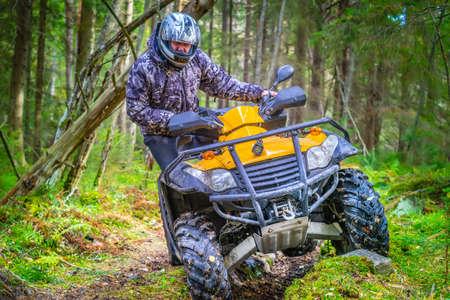 Quad biking. A stressful man rides a quad bike through the mud. Off-road riding on ATV. Turn on abyss on the ATV. Active sports. Extreme. Quad bike rental.
