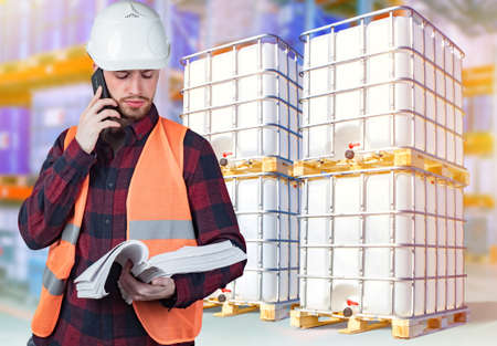 Warehouse of chemical products. Storage of tanks with chemical liquids. A storekeeper with documents in hand is talking on a mobile phone. Warehouse business.