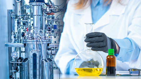 Microbiological laboratory. Equipment for the synthesis of new drugs. Pharmacology. Chemist's hand, flask and vial on the background of a laboratory bioreactor. Archivio Fotografico