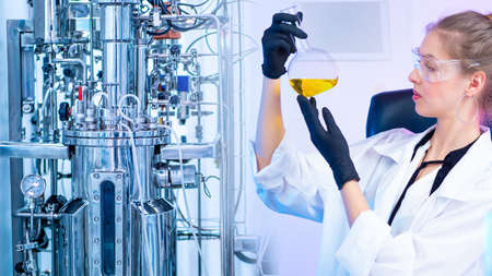 The girl looks at the yellow chemical liquid in the flask. Development of new vaccines. Bioreactor in the chemical laboratory. Research in the field of Microbiology.