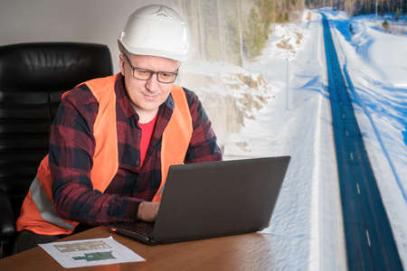 A construction worker works on a laptop against the background of a country road. Construction of cottages in rural areas. Supply of materials. An engineer is working on a country house project.