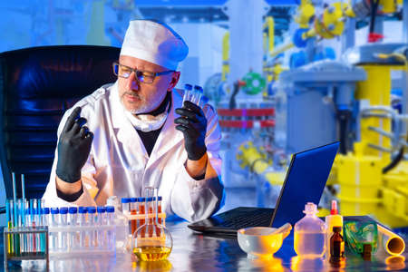 Chemist at his Desk in the background of the enterprise shop. Quality control of raw materials for production. Checking the finished product in the laboratory. Control Department at the enterprise.