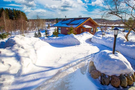 A snow-covered path leads to the cottage. View of the house on a Sunny winter day. Winter in the countryside. Building on the background of a winter landscape.