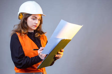 Civil engineer. The girl makes notes in the construction documentation. A woman in a construction helmet and an orange vest. Engineer in the field of construction. A girl with documents.