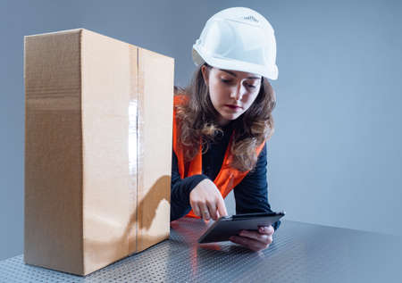 Delivery service. The woman next to the box. A girl in a hard hat and orange vest with an electronic tablet in her hands. The layout of the orders.