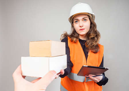 Delivery of goods from the warehouse. The girl passes the boxes to another person. A woman in a hard hat and orange vest with an electronic tablet in her hands.