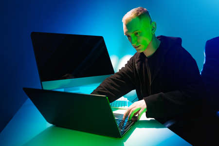 Computer addiction. A man works at a computer. The face of the person behind the laptop is illuminated in green light. Excessive fascination with gadgets.