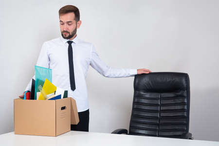 Job loss. An office worker with his cardboard box leaves his job. Last day at work. A frustrated office worker is fired. Unemployment concept. The dismissed employee leaves the office.