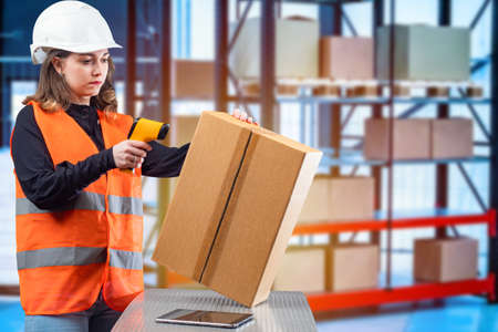 The work of the storekeeper. A girl in a reflective vest works in a warehouse. The girl reads data from a cardboard box with a special scanner. Acceptance of goods to the warehouse.