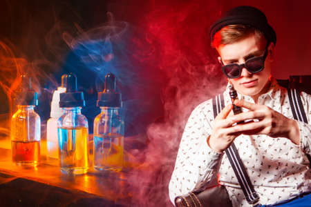 A thoughtful Vaper next to bottles of e-cigarette liquids. VAPE shop. Vaping accessories. A man with an e-cigarette on a red background.