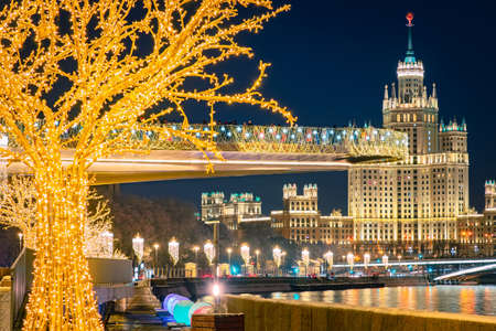 Christmas in Moscow. Moscow is decorated for the New year. Christmas decorations in the Russian capital. Festive evening in Moscow. People admire the festive city. Soaring bridge and Stalin high-rise