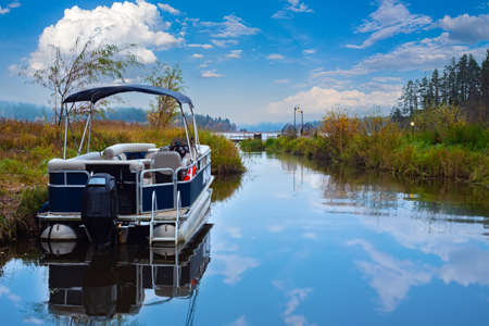 The boat is on the shore of the lake. Water trips. Motor boat against the beautiful sky. Boat without people on the background of the autumn landscape. Boating in the fall. Archivio Fotografico