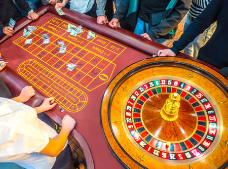 Waiting for win at the casino. A table with a tape measure. Gambling for money. People place bets on roulette. Underground gambling. Casino with roulette. Standard-Bild