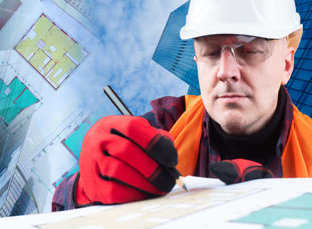 Civil engineer. A man in a hard hat on the background of buildings. The engineer makes notes in the construction documentation. A man in a reflective vest and work gloves.