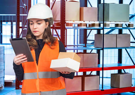 Woman Search for the desired box using an electronic tablet. Woman with boxes in her hands against the background of the warehouse. 版權商用圖片