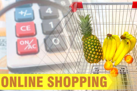 Yellow lettering on the background of a shopping cart with food. Online grocery store. Buying products with home delivery.