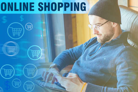 A man makes purchases in an online store. Blue text Online shopping and a buyer. A man with a tablet on the background of shopping icons. Online purchases and payments.